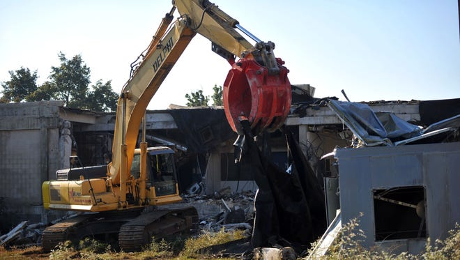 An equipment operator separates the debris as demolition begins on Newcomb Hospital Monday, Oct. 17, 2016 in Vineland.