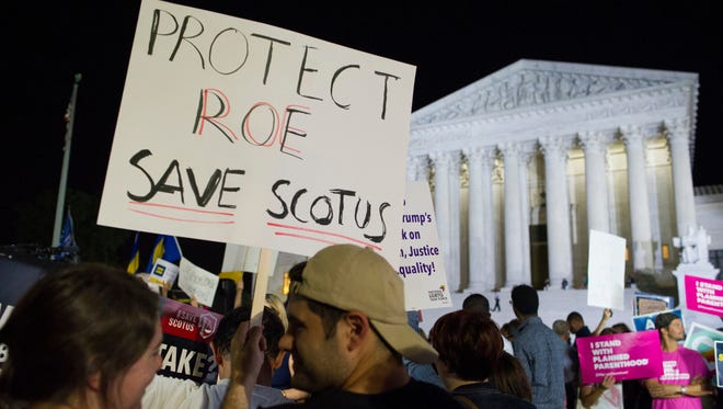 A demonstrator holds a sign as protesters gather in front of the Supreme Court in Washington after President Donald Trump announced Brett Kavanaugh as his Supreme Court nominee.