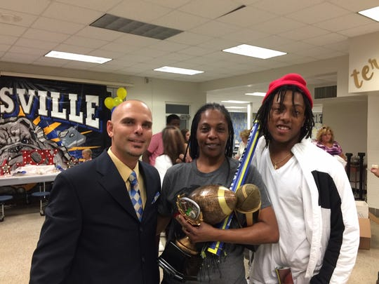 """Coach Matt Diesel, left, with Dwight Bobby Bruce Jr. aka Bobby Bruce, and his mother Maria Roe, at a Titusville football awards banquet in 2016. Bruce appeared in season three of """"Last Chance U"""" on Netflix."""