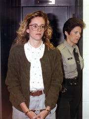 Reporter Libby Averyt is escorted in handcuffs to the Nueces County Jail by a correctional officer in 1990.