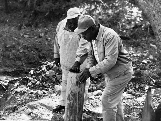 Robert Jones, left, examines a casing during a Sept.