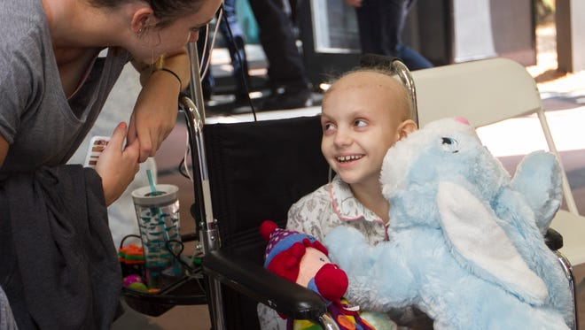 Cali Trepkowski, 9, smiles after getting lost of gifts from motorcyclists participating in the 13th annual Easter Bunny Toy Run on Saturday at Golisano Children's Hospital in south Fort Myers.