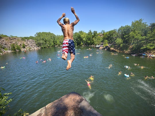 A diver takes flight from a cliff high over the 116-foot-deep water of Quarry 2  in Quarry Park & Nature Preserve in a Times file photo.