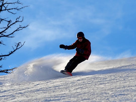 A snow boarder carves some turns at Showdown Montana.