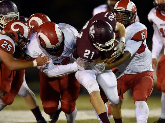Shane Welshans of Henderson County is stopped on the run by Sean Cleasant, left, and Andre Teague of DuPont Manual during the second quarter of the game at Colonel Stadium in Henderson Friday.