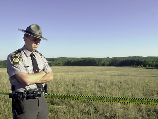 A Pennsylvania State Trooper stands guard at the crash