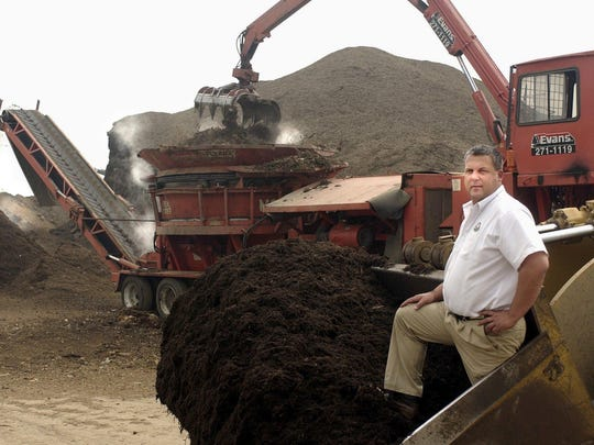 Douglas Evans poses in front of a loader full of mulch