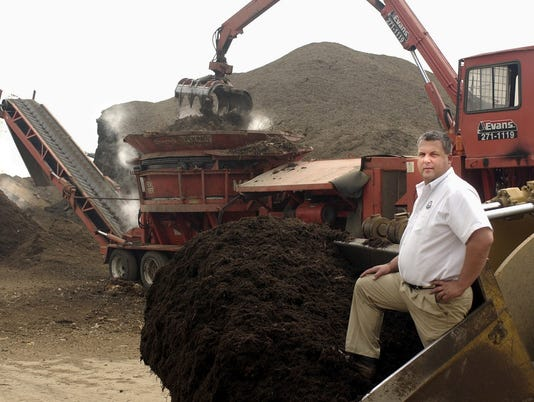 MULCHMAN METRO - Evans Landscaping owner and president Doug Evans stands on some black mulch from a front loader's bucket near one of the company's mulch hoppers at the Evan's Landscaping mulch production facility in Newtown April 30, 2003. Evans Landscaping uses 30 acres for mulch production. Photo by Michael Snyder/Cincinnati Enquirer