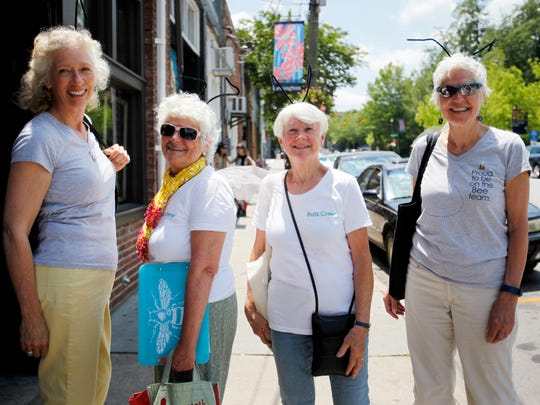 From left, Bee City USA members Libba Tracy, Pamela Cauble, Kristina Pontin and leader Phyllis Stiles walk downtown to spread the word about their organization by placing decals of bees in the windows of local businesses.