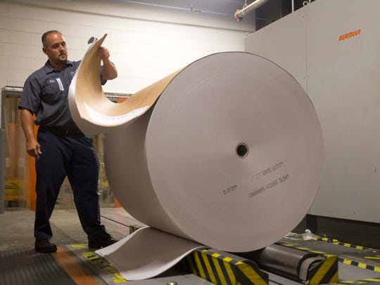 John Phillips opens a roll of paper in the reel room