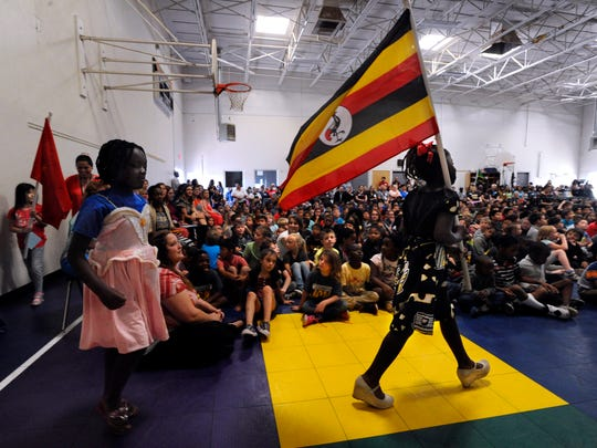 Winner Moligi carries the flag of Uganda on May 18, 2017, at Lee Elementary School. Students from 19 countries carried the flags of the nations from which their families came during an assembly celebrating the school's international diversity. Abilene has become home to more than 1,200 refugees.