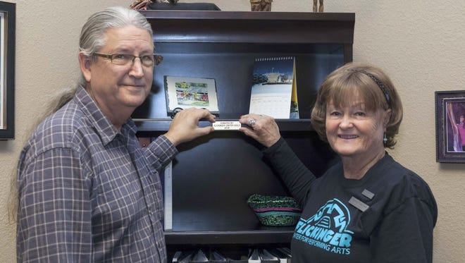 Flickinger Center Executive Director Jim Mack and Flickinger Guild Vice President Ann Smith apply the donation plaque to office furniture.