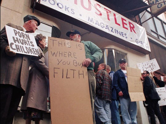 Anti-pornography protesters stand outside Hustler News and Gifts where Hustler magazine publisher Larry Flynt signs magazine copies at the opening of his new store in downtown Cincinnati October 22, 1997.