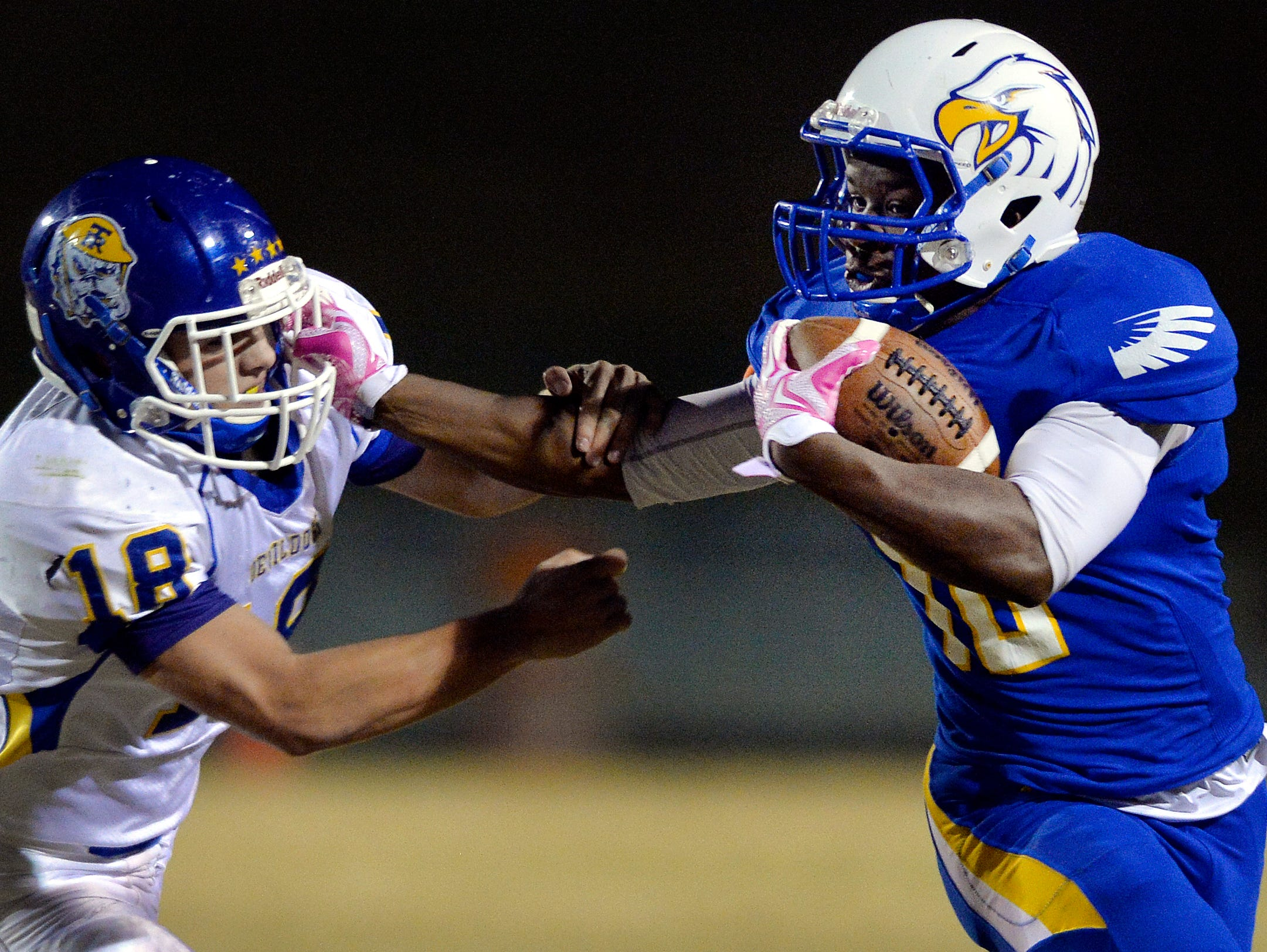 Eastside's Jovani Lawton (10) uses a stiff-arm to get past Travelers Rest's Holland Echols (18) on Oct. 23, 2015.