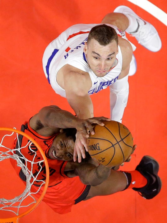 Portland Trail Blazers forward Ed Davis, below, shoots as Los Angeles Clippers forward Sam Dekker defends during the first half of an NBA basketball game, Tuesday, Jan. 30, 2018, in Los Angeles. (AP Photo/Mark J. Terrill)