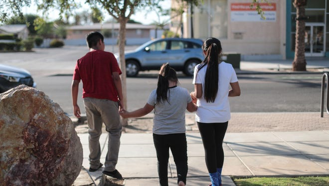 Three siblings, part of a family of nine kids, the youngest, pictured in the middle is a U.S. citizen and has Down Syndrome, leave the TODEC Legal Center in Coachella to be driven home on Thursday, July 5, 2018. Their mother was arrested and deported.