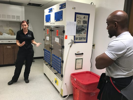 Forensic specialist Dianna Arndt uses the fingerprint of Citizens Police Academy participant Bennie Wylie Jr., right, to demonstrate the fingerprinting process.