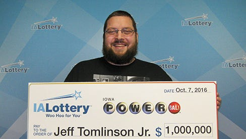 Jeff Tomlinson Jr. of Coralville with a giant $1 million Poweball Prize check.
