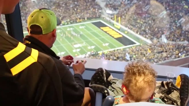 Will Kohn watches a Hawkeyes game on the 12th floor of the Stead Family Children's Hospital. The fans at Kinnick Stadium wave to the children in the hospital.