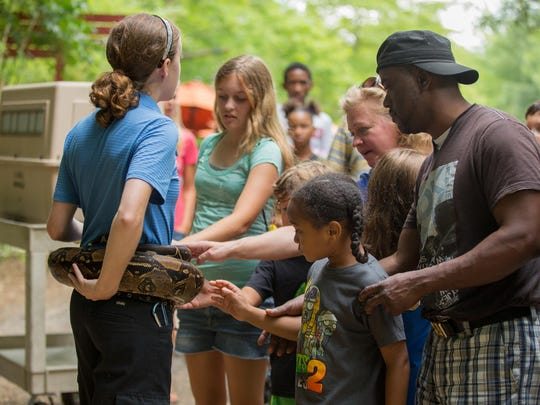 "Memberships make sense if you plan to go to an attraction more than two or three times a year. Here, Nashville Zoo visitors take part in an ""Animal Encounter"" session with one of the zoo's snakes."