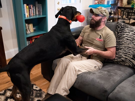 Tony Swett plays with his service dog Cooper in his Spartanburg home on Tuesday, April 5, 2017.