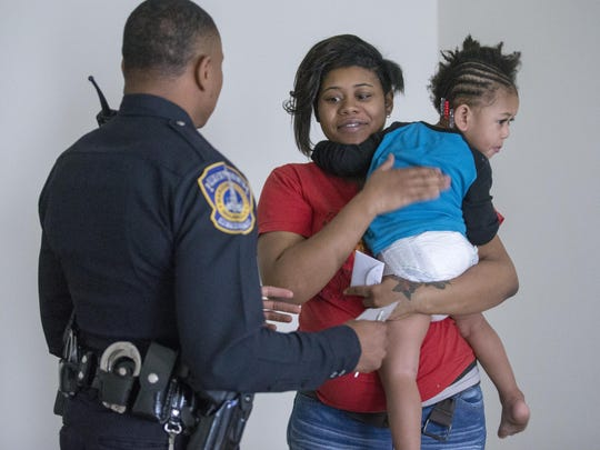 """Deaujahnee Johnson holds toddler son Kneepo Isabell Jr. as she talks with visiting IMPD officer Jason Mitchell. During an operation called """"Ho Ho 5-0,"""" officers delivered $100 gift cards on Monday, Dec. 21, 2015, to 200 people in need during the holiday season. An anonymous Indianapolis businessman donated $20,000 to the Indianapolis Public Safety Foundation for the community outreach effort."""