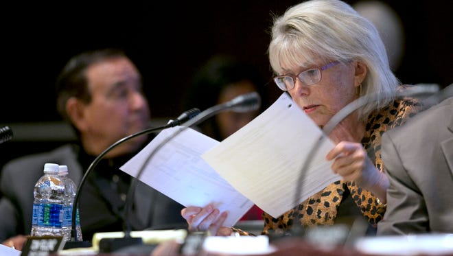 Lynn Schenk, a member of the California High-Speed Rail Authority, looks over papers at a rail board hearing Tuesday in Sacramento. Schenk and fellow board member Ernest Camacho, left, were critical of the budget overruns in the construction of the first leg of the rail system.