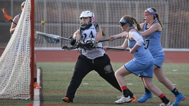 Eastridge goalie Nikki Larsen keeps the ball out of the net with a goal crease save as Gananda's Shelby Maiorano, right, and Allison Stark look to score during their game Monday, April 18, 2016 at Eastridge High School in Irondequoit.