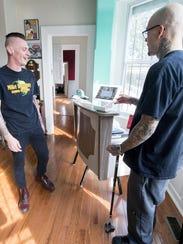 Steve Klinedinst, left, pays John Shilling for a haircut