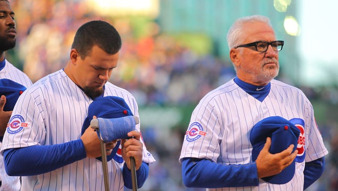 Chicago Cubs left fielder Kyle Schwarber (left) and manager Joe Maddon (right) during the national anthem prior to a game against the Cincinnati Reds at Wrigley Field.