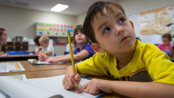 Ronan McGeough works on an assignment in 2013 during his all-day kindergarten class at the Litchfield Traditional Academy.