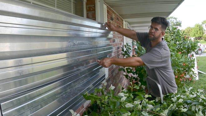 Allen Abreu helps  his mother Maria put up hurricane shutters in advance of Hurricane Matthew.