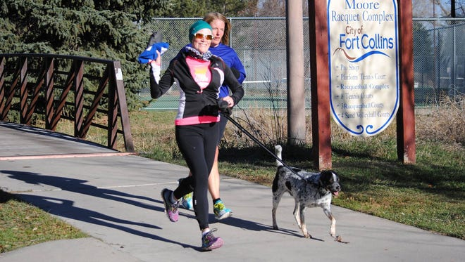 Kirsten Schuster, who is undergoing treatment for Stage IV cervical cancer, runs with her dog in a recent Fort Collins Running Club Tortoise and Hare Series race through Rolland Moore Park.