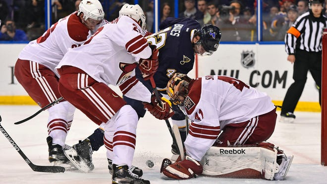 Feb 10, 2015: Arizona Coyotes goalie Mike Smith (41) attempts to cover the puck shot by St. Louis Blues center David Backes (42) during the second period at Scottrade Center.