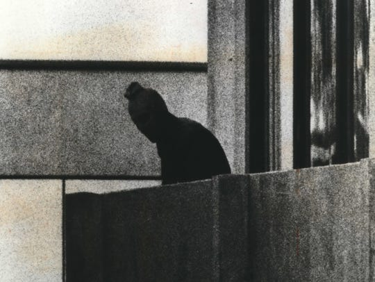 A commando appears with a mask on the balcony of a