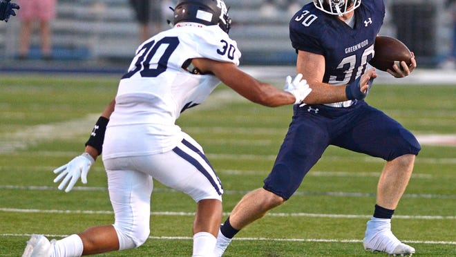 Greenwood running back Hunter Wilkinson, right, cuts away from a Springdale Har-Ber defender during a game on Friday, Sept. 11 in Smith-Robinson Stadium.