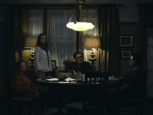 Charlie (Milly Shapiro, left), Annie (Toni Collette), Steve (Gabriel Byrne) and Peter Graham (Alex Wolff) fall under a family curse in 'Hereditary.'