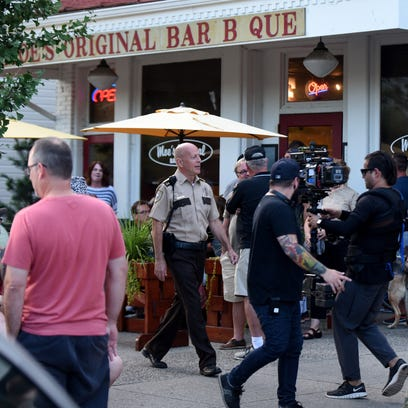 Bruce Willis walks down East Broadway as a film crew