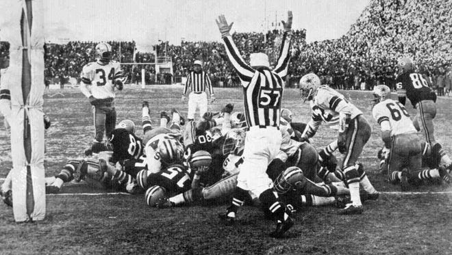 Green Bay Packers quarterback Bart Starr (15) at left foreground, digs his face across the goal line to score the winning touchdown against the Dallas Cowboys to bring the Packers their third consecutive NFL championship on Dec. 31, 1967 in Green Bay. The Packers defeated the Cowboys, 21-17.