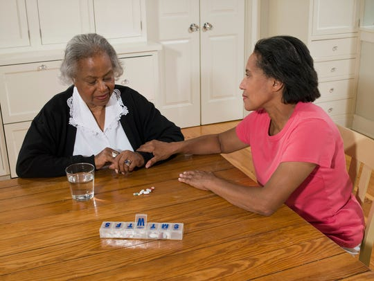 Senior woman with daughter sitting at table with pill