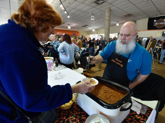 Dave Hess of Laurel serves his chili at the chili cook off contest at Rommel Harley-Davidson in Seaford.