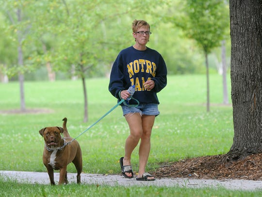 Tami Larson walks Roxzie, a two-year-old pit bull,