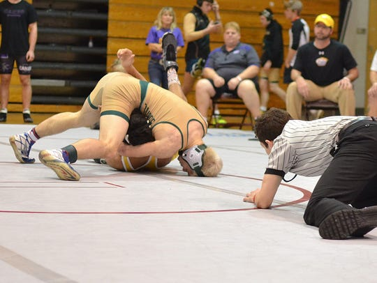 Lincoln's Eli Crum pins his opponent.