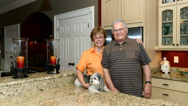 Barbara and Harry Moore, with their dog Tango, stand in the kitchen of their loft in the Clarke Hardware Building in downtown Hendersonville.