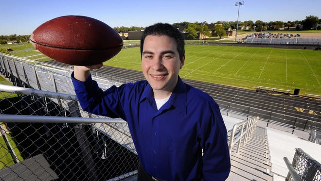 "Jesse Goldberg-Strassler, author of ""The Football Thesaurus"" and announcer for Lansing Lugnuts, at the Waverly High football field."