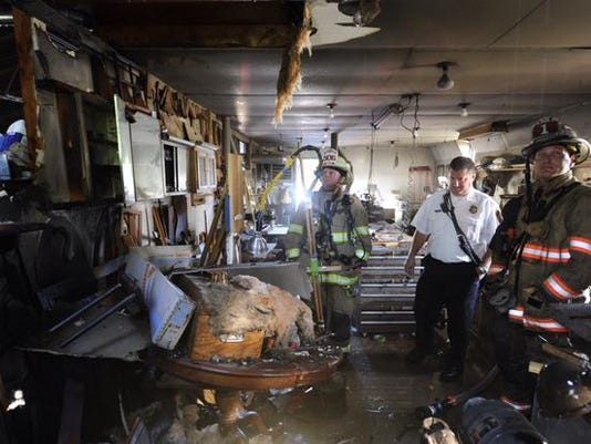 Fire officials check out damage to a workshop in West Manchester Township on Friday.