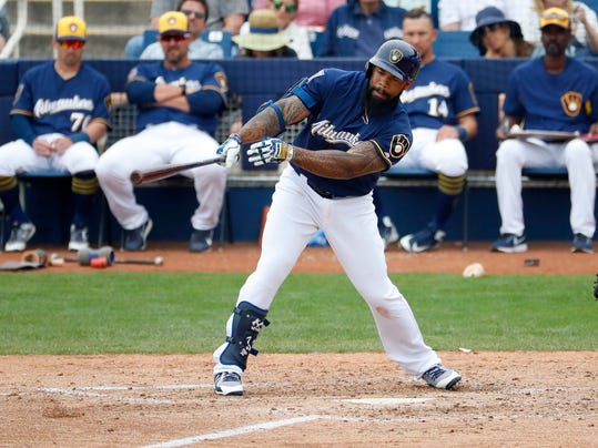 Milwaukee Brewers' Eric Thames follows through on an RBI-base hit against the Colorado Rockies during the fourth inning of a spring training baseball game Saturday, March 10, 2018, in Phoenix. (AP Photo/Matt York)