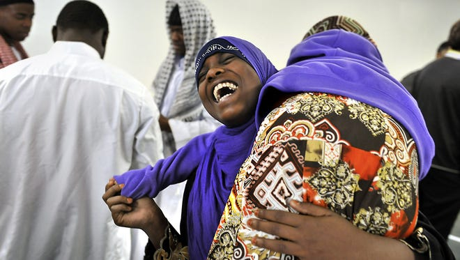 Fardowsa Omar, 13, laughs as she picks up cousin Muniira Barre, 7, after Friday prayers at the Wali Mahmoud Islamic Center.  Rod Sanford/LSJ Fardowsa Omar, 13, laughs as she picks up her cousin Muniira Barre, 7, after Friday prayers at  the Wali Mahmoud Islamic Center on the west side of Lansing on April 6, 2012.  The center is in a small converted corner store and was formerly a Nation of Islam Temple.   In the past few years a significant number of Somali immigrants who came to Lansing as refugees have joined the center.