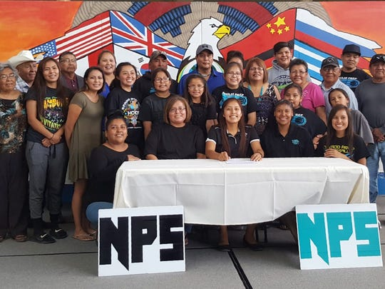 Navajo Prep's Harlei Haceesa, center, signs a letter of intent to play basketball for the University of the Southwest on Wednesday at Navajo Prep.