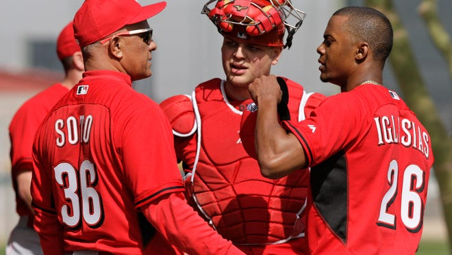 Former Reds pitcher Mario Soto, special assistant to the general manger, and catcher Devin Mesoraco talk with pitcher Raisel Iglesias on Thursday.